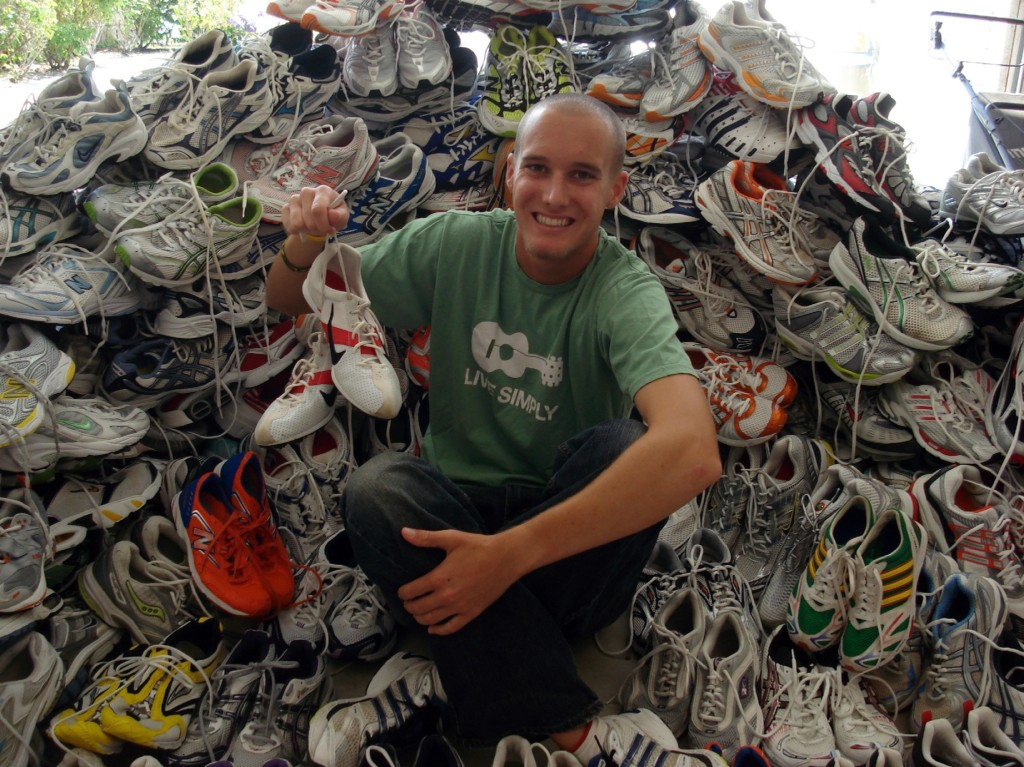 Greg with a pile of running shoes about to be sent off to kids in Africa.